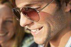 微笑的年轻人佩带的太阳镜 免版税图库摄影