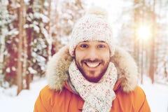 微笑的年轻人在多雪的冬天森林里 图库摄影