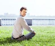 微笑的年轻人在绿色草坪放松 免版税库存照片
