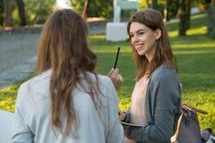 微笑的年轻人坐户外在公园文字笔记的两名妇女 库存照片
