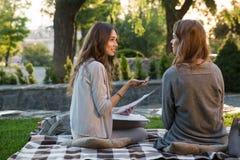 微笑的年轻人坐户外在公园文字笔记的两名妇女 图库摄影