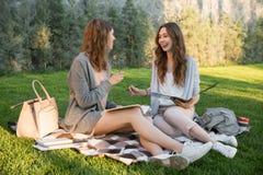 微笑的年轻人坐户外在公园文字笔记的两名妇女 库存图片