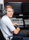 微笑的年轻人混合的音频在录音室 库存照片