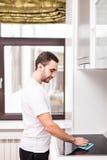 微笑的年轻人清洁厨房画象在房子里 库存图片