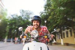 微笑的年轻人骑马小型摩托车 免版税库存照片
