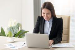 微笑的年轻企业夫人与膝上型计算机一起使用,看scre 库存图片