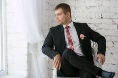 微笑的年轻商人坐一把白色椅子 图库摄影