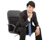 微笑的年轻商人坐椅子 免版税库存照片