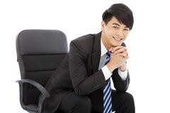 微笑的年轻商人坐椅子 免版税图库摄影