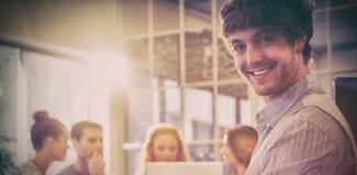 微笑的年轻商人画象与同事的 库存照片