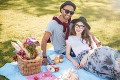微笑的年轻夫妇有在草坪的野餐在公园 免版税库存图片