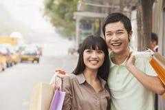 微笑的年轻夫妇,北京,中国画象在公共汽车站的 免版税库存照片