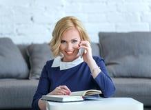 微笑的年轻女商人谈话与手机 库存图片