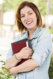 微笑的年轻女学生外面与书 免版税图库摄影