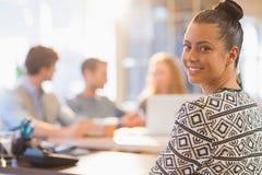 微笑的年轻女实业家画象有同事的 免版税库存照片