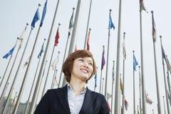 微笑的年轻女实业家画象有旗子的 库存图片
