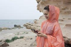 微笑的年轻女性短信的消息半身画象在手机的 库存图片