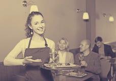 微笑的年轻女服务员问候顾客 库存照片
