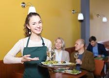 微笑的年轻女服务员问候顾客 免版税图库摄影