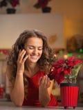 微笑的主妇谈的电话和使用与圣诞节上升了 库存图片