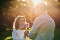给他微笑的妻子的年轻人开花在日落 图库摄影