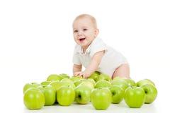 微笑的婴孩和许多绿色苹果 免版税库存图片