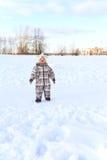 微笑的婴孩在天空看在冬天户外 免版税库存照片