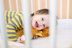 微笑的婴孩在白色床上 库存照片