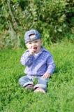微笑的婴孩坐草在夏天 图库摄影