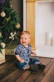 微笑的婴孩少年开会在壁炉附近的Chritmas树下 免版税图库摄影