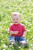 微笑的婴孩户外反对花 免版税库存照片