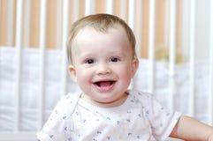 微笑的婴孩画象反对白色床的 免版税图库摄影