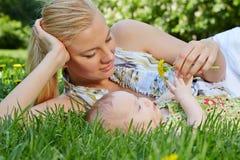 微笑的母亲在绿草斜倚在她的婴孩旁边 免版税库存图片