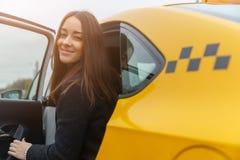 微笑的年轻深色的妇女在黄色出租汽车坐 库存图片