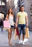 微笑的年轻爱恋的加上在城市的袋子 库存照片
