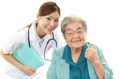 微笑的医生和资深妇女 免版税库存照片