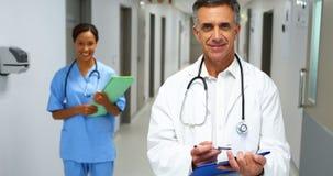 微笑的医生画象有站立在走廊的医疗报告的 影视素材