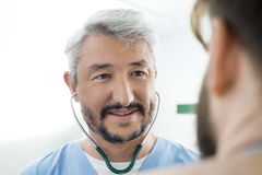微笑的医生Wearing Stethoscope在患者的While Looking 图库摄影