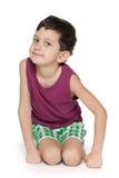 微笑的年轻男孩坐白色 免版税库存图片