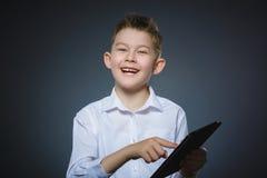 微笑的年轻男孩或少年有片剂个人计算机计算机的 免版税库存图片