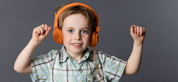 微笑的年轻男孩跳舞,听到在耳机的音乐 图库摄影