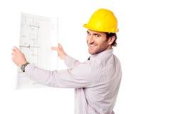 微笑的建筑工程师回顾的图纸 图库摄影