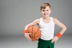微笑的活跃男孩画象运动服的有篮球球的 库存图片