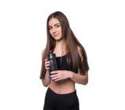 微笑的年轻运动的妇女画象有水摆在演播室的一个瓶的隔绝在白色背景 免版税库存照片