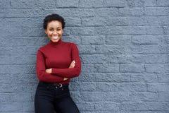 微笑的年轻非裔美国人的妇女对灰色墙壁 库存照片
