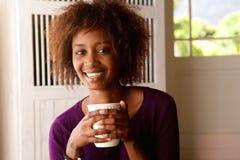 微笑的年轻非裔美国人的妇女饮用的咖啡 免版税图库摄影