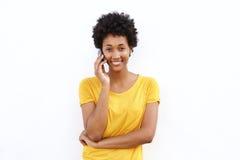 微笑的年轻非洲妇女谈话在手机 免版税库存图片