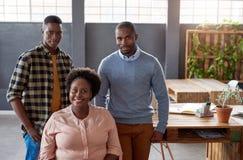 微笑的年轻非洲工友在工作在一个现代办公室 免版税库存照片