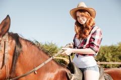 微笑的attrative少妇女牛仔骑乘马 免版税图库摄影
