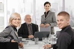 微笑的businessteam纵向在会议的 库存图片